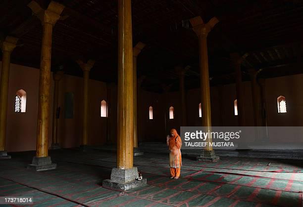 A Kashmiri Muslim woman prays inside the grand mosque Jamia Masjid during Ramadan in downtown Srinagar on July 17 2013 Islam's holy month of Ramadan...