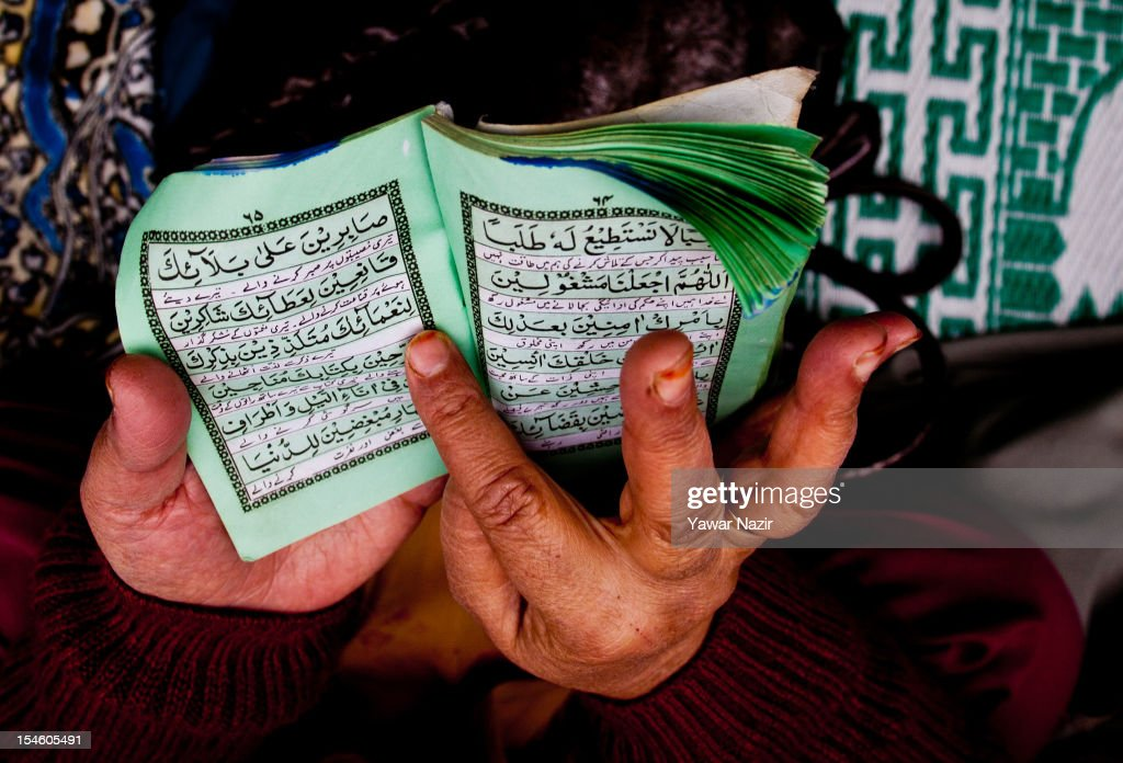 A Kashmiri Muslim woman reads Quranic verses at the entrance of the shrine of Khaniqahi mullah during a festival on October 23, 2012 in Srinagar, the summer capital of Indian administered Kashmir, India. Thousands of Muslims thronged to the shrine of Mir Syed Ali Hamadan to commemorate the anniversary of the death of the Sufi saint, Hamadan. He is believed to be responsible for the spread of Islam in Kashmir. The shrine gains a special significance on 6th of Zilhaj (last month of Muslim calendar), the death anniversary of Mir Syed Ali Hamadan. On this day, devotees visit the shrine in large numbers to pay a tribute to saint Hamadan.