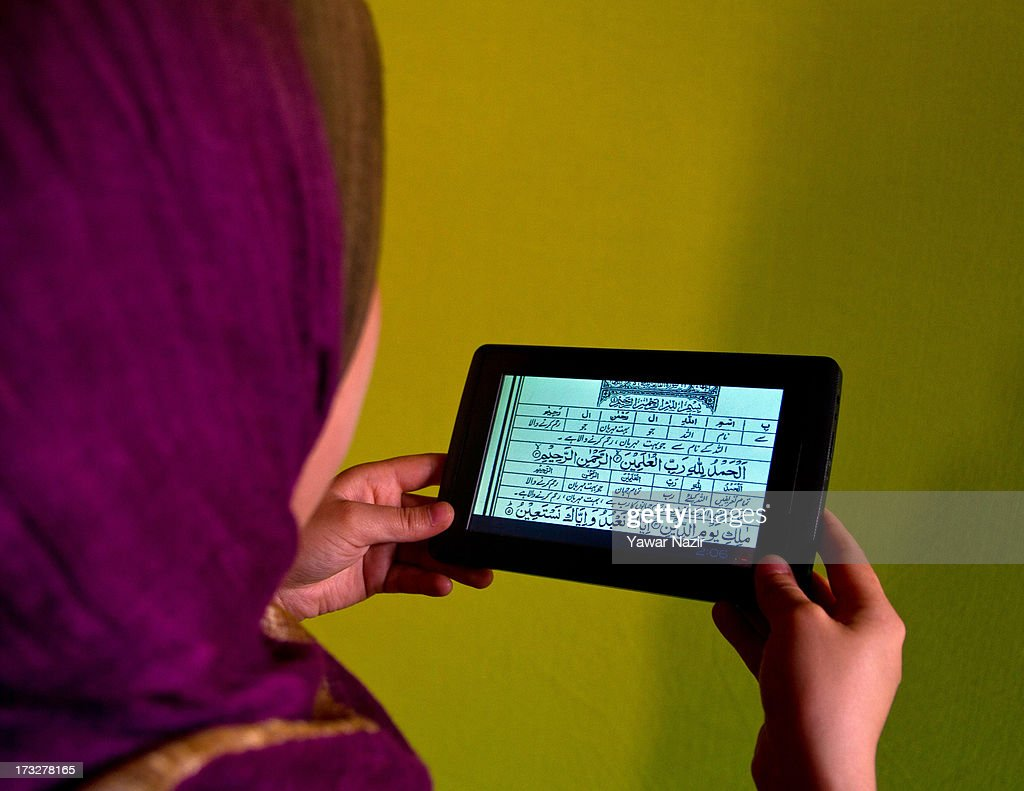 A Kashmiri Muslim woman reads the Quran on a tablet during Ramadan on July 11, 2013 in Srinagar, the summer capital of Indian administered Kashmir, India. Ramadan is the ninth month of the Islamic lunar calendar, during which Muslims believe the Quran was given to Prophet Muhammad. Muslims across the globe abstain from eating, smoking, and sex from dawn to dusk during the month. Besides spending more time praying, donating alms is mandatory. Every Muslim has to give 2.5 percent of their wealth and assets to the poor, and often give more.