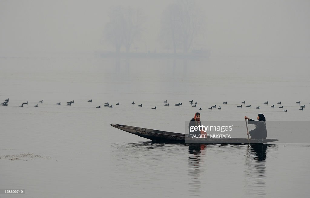 Kashmiri Muslim woman rides a shikara boat in Dal lake during a cold wave affecting Srinagar on December 13, 2012. A cold wave further tightened its grip in Jammu and Kashmir with most places in the state recording sub-zero temperatures. AFP PHOTO/ Tauseef MUSTAFA