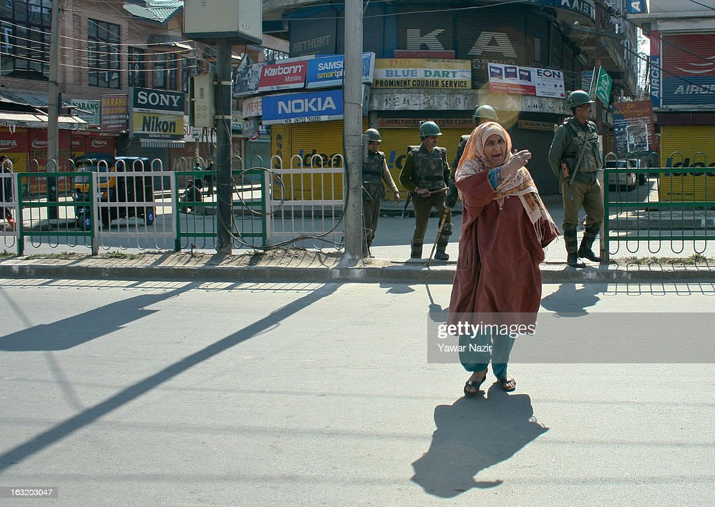 A kashmiri Muslim woman seeks permission from Indian paramilitary forces during a curfew like restriction on March 06, 2013 in Srinagar, the summer capital of Indian Administered Kashmir, India. Indian authorities imposed curfew like restrictions in most parts of Kashmir following a killing of kashmiri youth by Indian army in North Kashmir's Baramulla district yesterday.