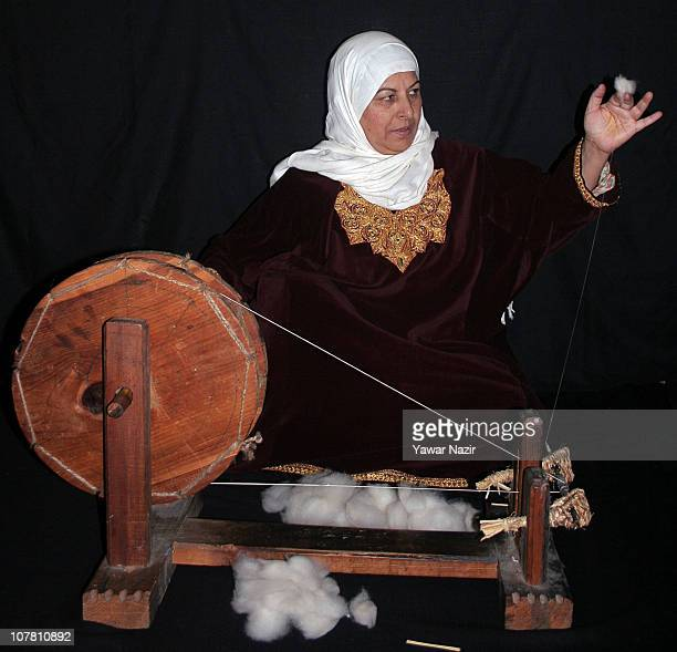 Kashmiri Muslim woman spins pashmina on a wheel used in shawl making on December 29 2010 in Srinagar the summer capital of Indian administered...