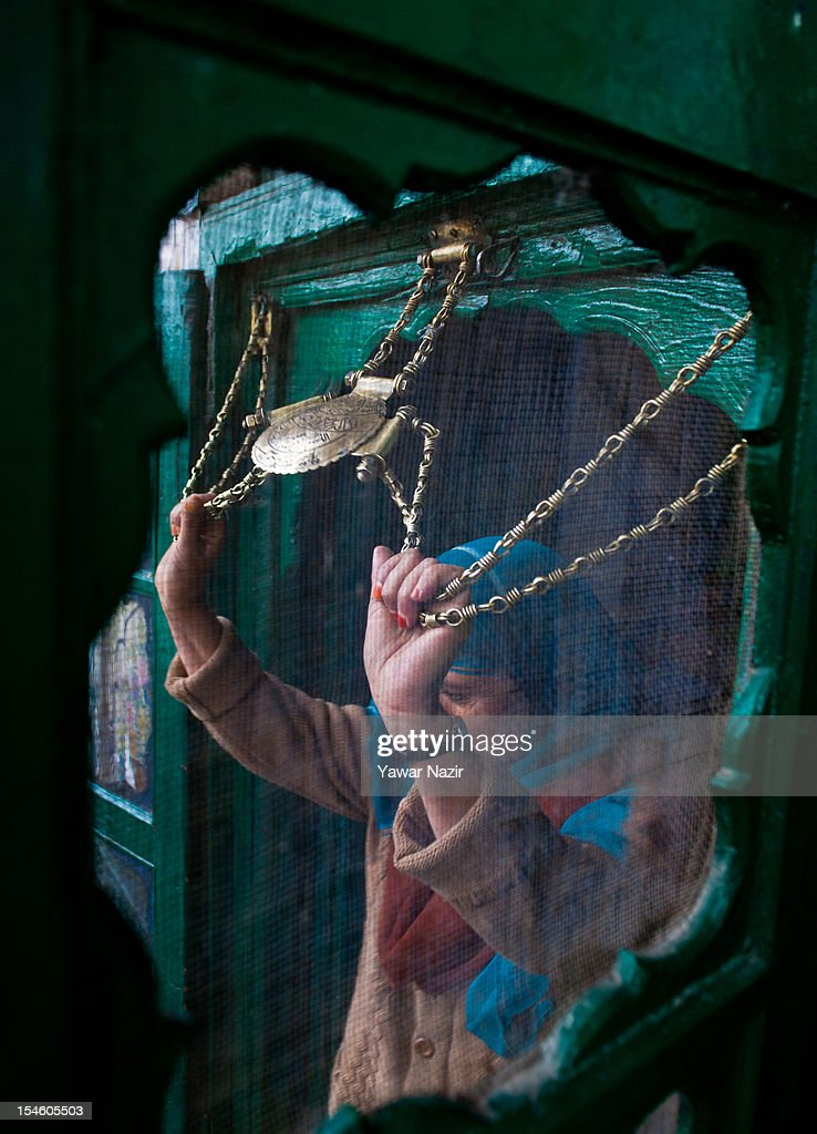 A kashmiri Muslim woman touches the chain engraved with Quranic verses at the entrance of the shrine of Khaniqahi mullah during a festival on October 23, 2012 in Srinagar, the summer capital of Indian administered Kashmir, India. Thousands of Muslims thronged to the shrine of Mir Syed Ali Hamadan to commemorate the anniversary of the death of the Sufi saint, Hamadan. He is believed to be responsible for the spread of Islam in Kashmir. The shrine gains a special significance on 6th of Zilhaj (last month of Muslim calendar), the death anniversary of Mir Syed Ali Hamadan. On this day, devotees visit the shrine in large numbers to pay a tribute to saint Hamadan.