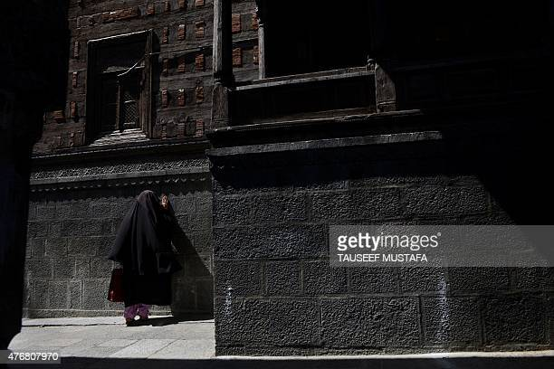 A Kashmiri Muslim woman touches the outer wall of the14th century shrine of Mir Ali Hamdani Khanqah e Moula in old town Srinagar on June 12 2015...