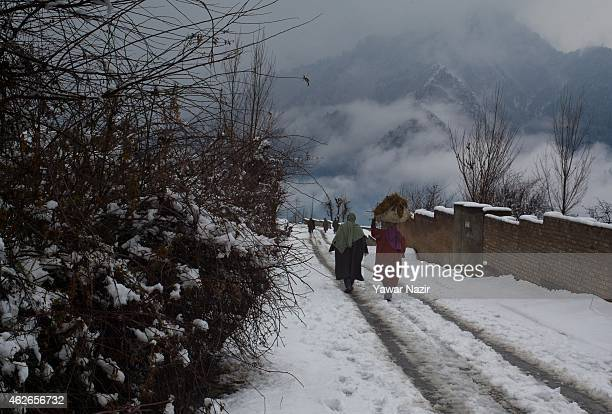 Kashmiri Muslim woman walks with cow dung manure on her head on a snow covered road after fresh snowfall on February 2 2015 in Srinagar Indian...