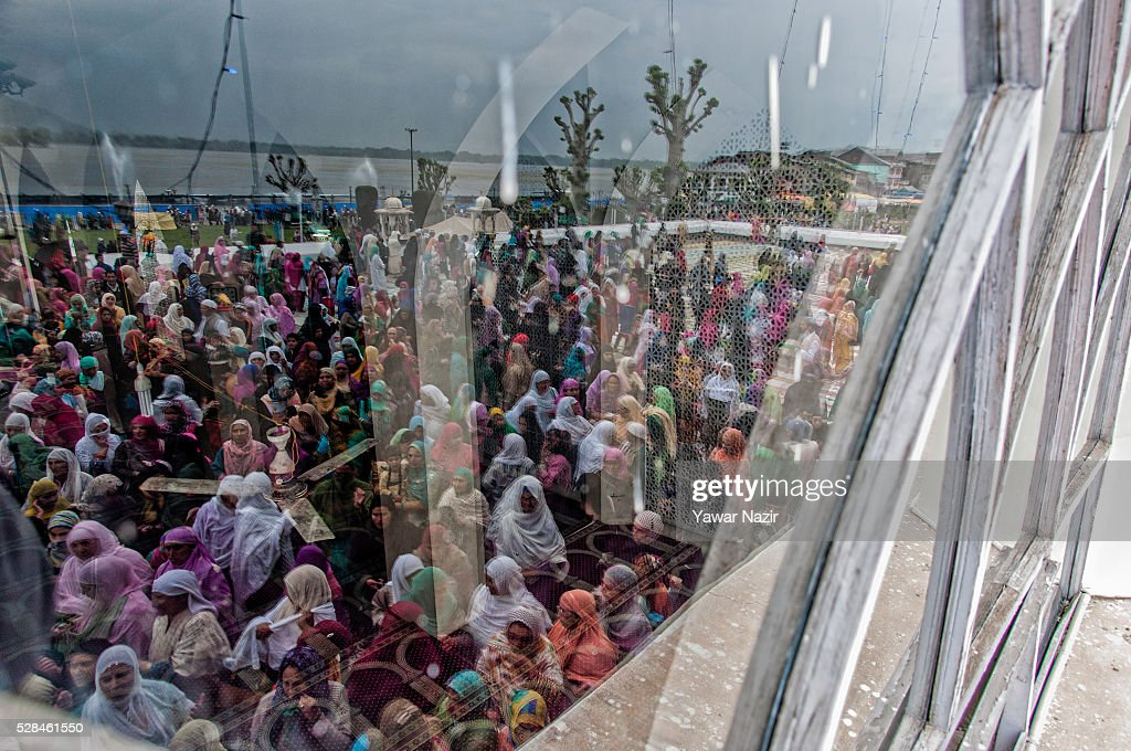 Kashmiri Muslim women are reflected on the glass as they pray while a head priest displays the holy relic believed to be the whisker from the beard...