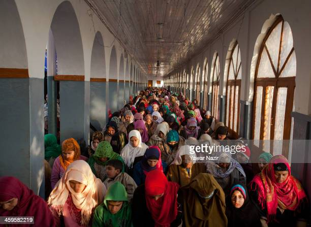 Kashmiri Muslim women devotees pray at the shrine of the Sufi saint Sheikh Hamza Makhdoom during a festival on December 28 2013 in Srinagar the...