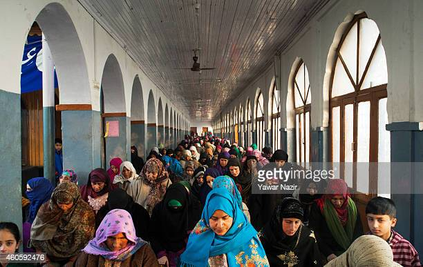 Kashmiri Muslim women devotees pray at the shrine of the Sufi saint Sheikh Hamza Makhdoom during a festival on December 17 2014 in Srinagar the...
