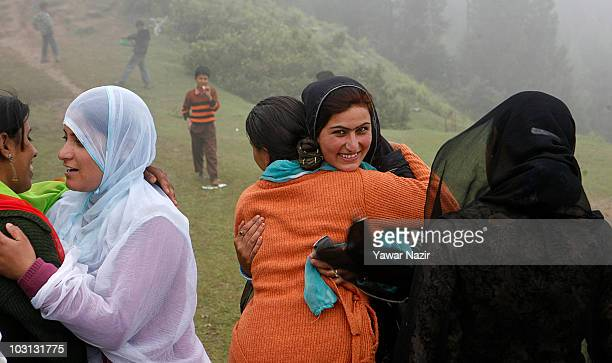 Kashmiri Muslim women embrace each other while walking towards the shrine of Baba Faridudin a Sufi saint to celebrate his festival on the borders of...