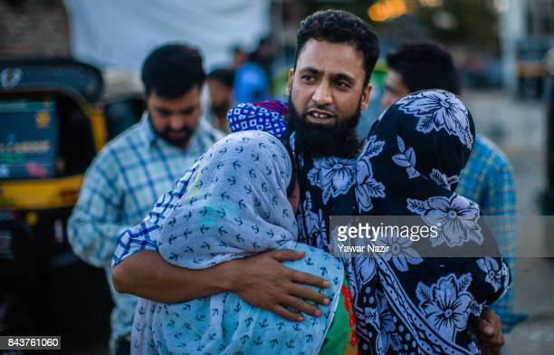 Kashmiri Muslim women hug their missing relative near the site after a grenade attack by suspected militants in a busy market on September 7 in...