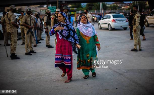 Kashmiri Muslim women look for their missing relatives near the site after a grenade attack by suspected militants in a busy market on September 7 in...