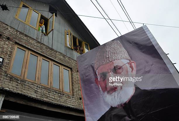 Kashmiri Muslim women look from the windows of there house as a poster of senior separatist leader of the All Parties Hurriyat Conference Syed Ali...