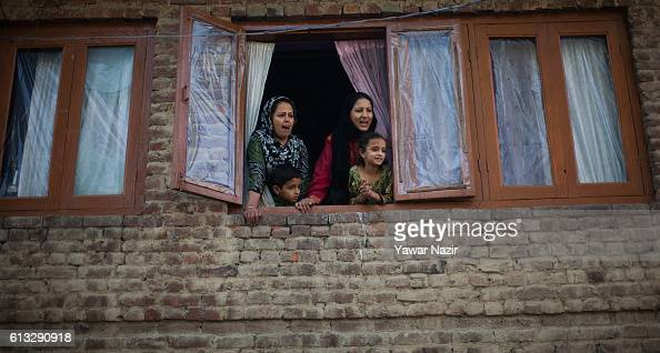 Kashmiri Muslim women look on as people carry the body of Junaid Ahmad who was reportedly killed by Indian government forces during his funeral on...