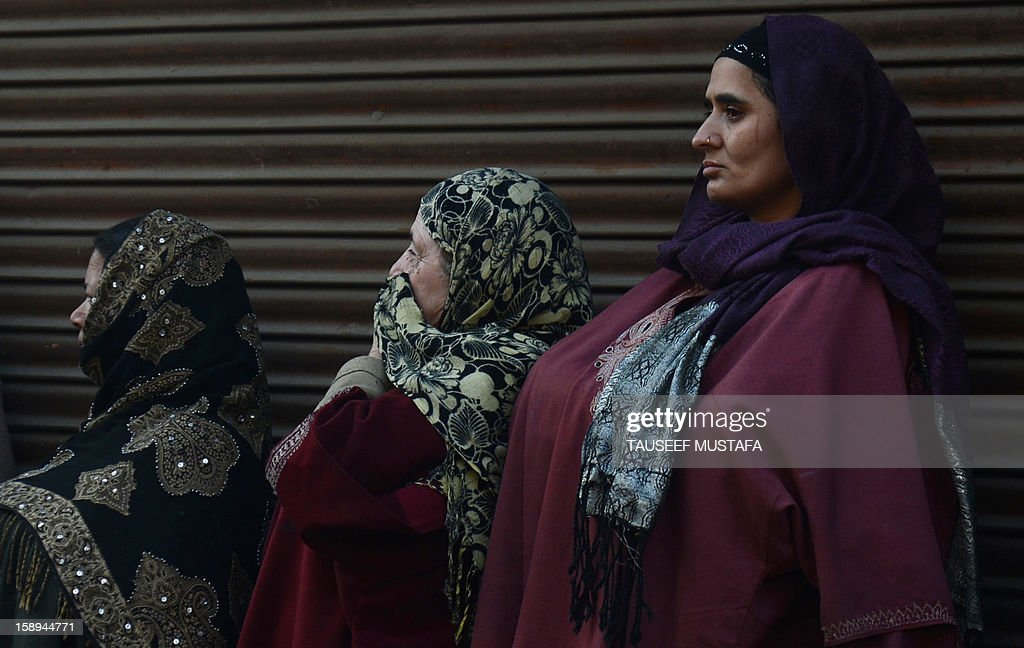 Kashmiri muslim women look on during a protest against a court verdict sentencing two Kashmiris to life imprisonment in Srinagar on January 4, 2013. The Muslim-majority region is in the grip of a 20-year insurgency against rule from New Delhi, which has left more than 47,000 people dead by the official count, a separatists put the toll twice as high. AFP PHOTO/ Tauseef MUSTAFA