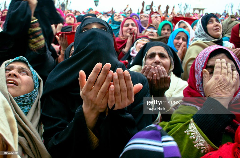 Kashmiri Muslim women look towards a cleric displaying the holy relic believed to be the hair from the beard of the Prophet Mohammed at Hazratbal shrine on the Friday following Eid-e-Milad , or the birth anniversary of Prophet Mohammad on February 01, 2013 in Srinagar, the summer capital of Indian administered Kashmir, India. Thousands of Muslims from all over Kashmir visit the Hazratbal shrine in Srinagar to pay obeisance on the Friday following Eid-e-Milad , or the birth anniversary of Prophet Mohammed. The shrine is highly revered by Kashmiri Muslims as it is believed to house a holy relic of the Prophet Mohammed. The relic is displayed to the devotees on important Islamic days such as the Eid- Milad when Muslims worldwide celebrate.