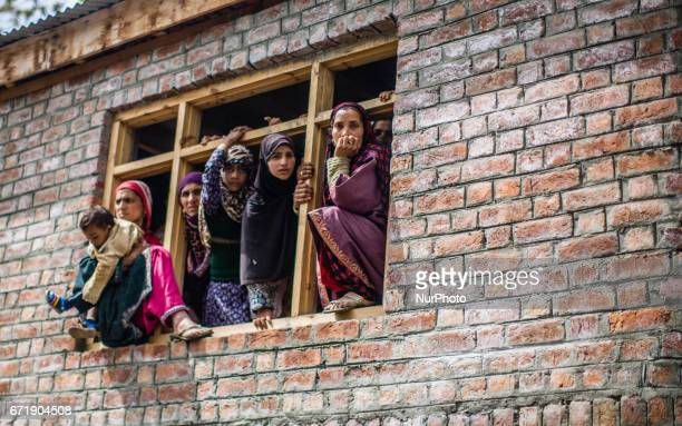 Kashmiri Muslim women look towards the body being carried by the men of Younis Maqbool Ganie a pro Kashmir rebel killed in a gun battle with Indian...