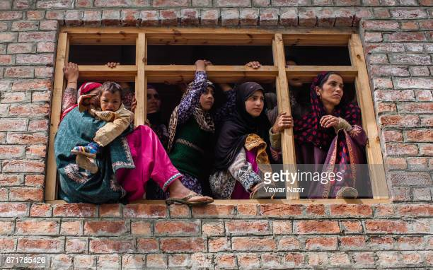 Kashmiri Muslim women look towards the body of Younis Maqbool Ganie a pro Kashmir rebel killed in a gun battle with Indian government forces being...