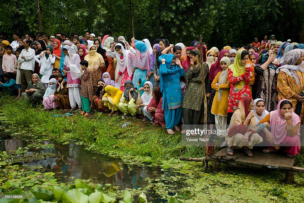 Kashmiri Muslim women look towards volunteers and rescuers search for survivors in the water after a footbridge collapsed into the water on August 11, 2012 in Srinagar, the summer capital of Indian administered Kashmir, India. According to witnesses and locals many people were injured some of them critically after an old makeshift foot bridge partially crumbled down due to overweight, in the interiors of Dal Lake .