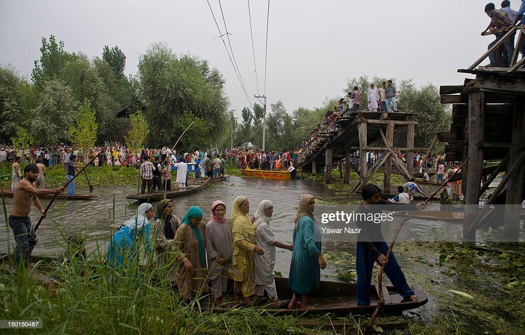 Kashmiri Muslim women look towards volunteers and rescuers searching for survivors in the water after a footbridge collapsed into the water collapsed into the water on August 11, 2012 in Srinagar, the summer capital of Indian administered Kashmir, India. According to witnesses and locals many people were injured some of them critically after an old makeshift foot bridge partially crumbled down due to overweight, in the interiors of Dal Lake .