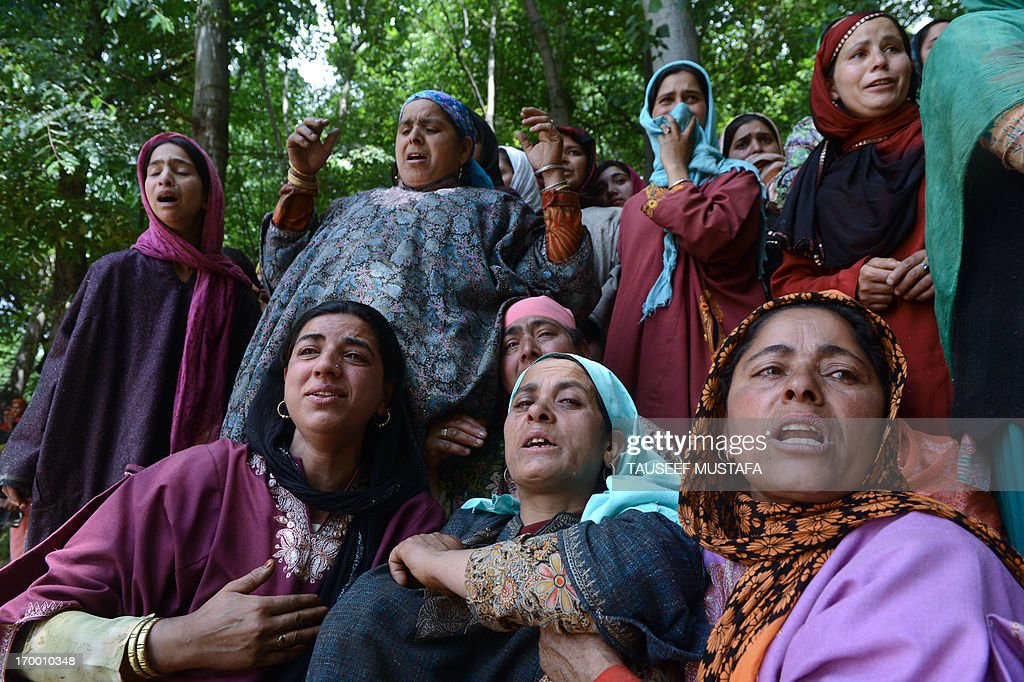Kashmiri Muslim women mourn during the funeral of self styled divisional commander of Jaish-e-Mohammad (JEM), Altaf Baba alias Gazi Baba at Algar-Kandi in Pulwama district, some 55 kms south of Srinagar on June 6, 2013. The encounter in Pulwama district of south Kashmir entered the second day as security forces exchanged fresh fire with holed-up militants in the wee hours. AFP PHOTO/Tauseef MUSTAFA