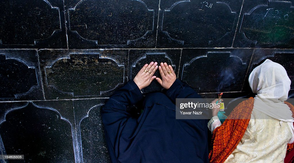 Kashmiri Muslim women pray by touching the wall at the shrine of Khaniqahi mullah during a festival on October 23, 2012 in Srinagar, the summer capital of Indian administered Kashmir, India. Thousands of Muslims thronged to the shrine of Mir Syed Ali Hamadan to commemorate the anniversary of the death of the Sufi saint, Hamadan. He is believed to be responsible for the spread of Islam in Kashmir. The shrine gains a special significance on 6th of Zilhaj (last month of Muslim calendar), the death anniversary of Mir Syed Ali Hamadan. On this day, devotees visit the shrine in large numbers to pay a tribute to saint Hamadan.