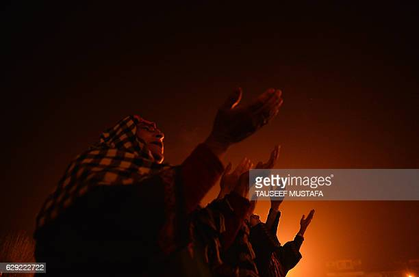 TOPSHOT Kashmiri Muslim women react as a priest displays a relic believed to be a hair from the beard of Prophet Muhammed during EideMiladunNabi the...