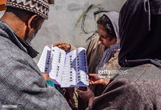 Kashmiri Muslim women search their names in the voting list before casting their votes during the elections of the lower house of the Indian...