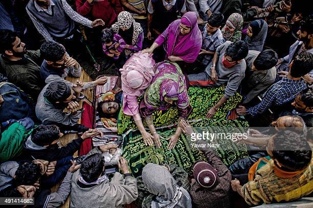 Kashmiri Muslim women touch the body of suspected Pakistani militants killed in a gun battle with Indian government forces during their funeral on...