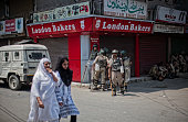 Kashmiri Muslim women walk as Indian government forces guard a deserted road following violence that has left over 46 people dead and thousands...
