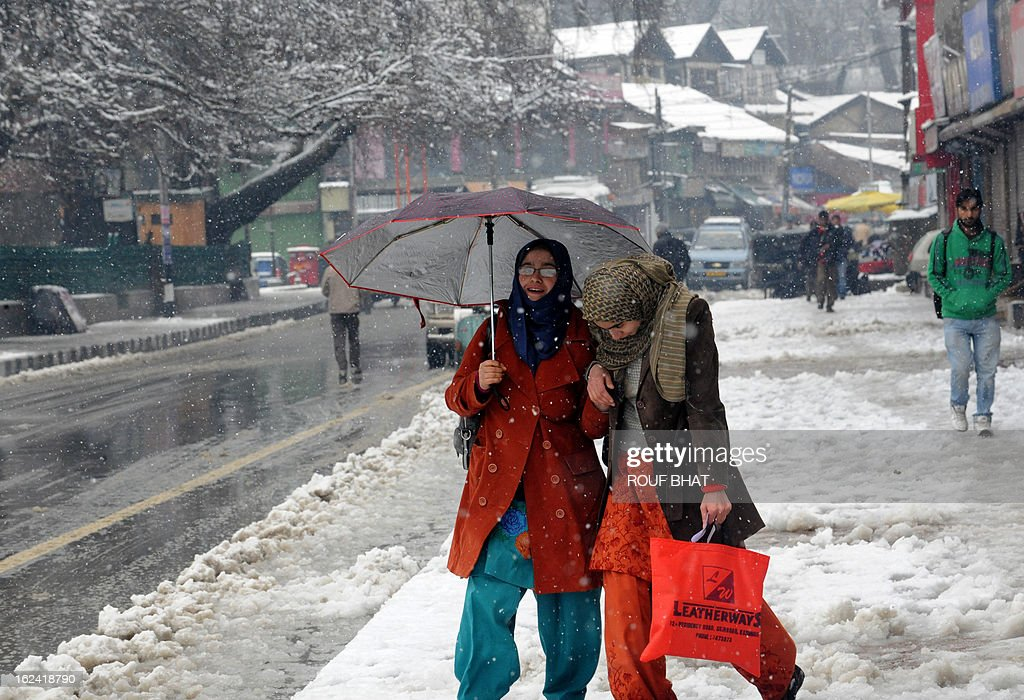 Kashmiri Muslim women walk during a snow fall in Srinagar on February 23, 2013. The Jammu-Srinagar National Highway remained closed for the second day as fresh snowfall across Kashmir prompted authorities to issue an avalanche warning in higher reaches of the Valley. AFP PHOTO/ Rouf BHAT