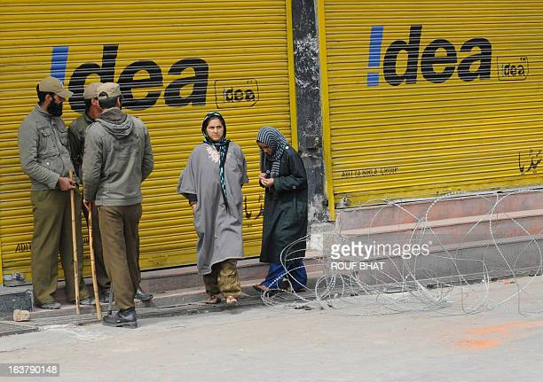 Kashmiri Muslim women walk past Indian policemen standing guard during the third day of a curfew imposed on the Kashmiri summer capital in Srinagar...
