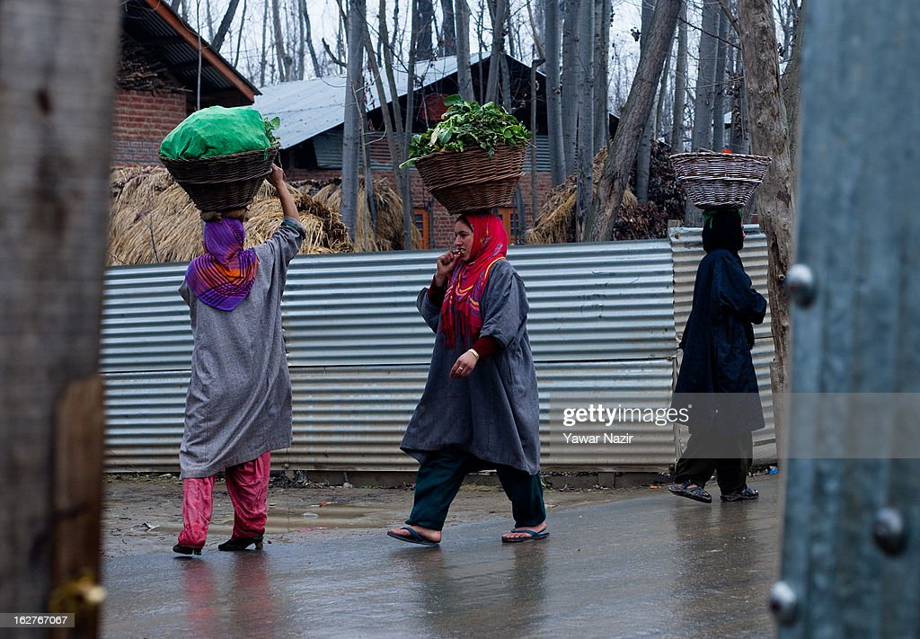 Kashmiri Muslim women walk with baskets filled with vegetables on their heads in a village on February 26, 2013 in Budgam west of Sringar, the summer capital of Indian Administered Kashmir, India. Kashmir has been a contested land between nuclear neighbors India and Pakistan since 1947, the year both the countries attained freedom from the British. Since 1947 the ownership of Kashmir has been disputed between Pakistan, India and China.