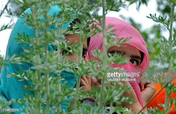 Kashmiri Muslim women watch the funeral of alleged Pakistanbased JaisheMohammad militants Qari Zubair and his bodyguard Muhammed Imran Khan at Keller...