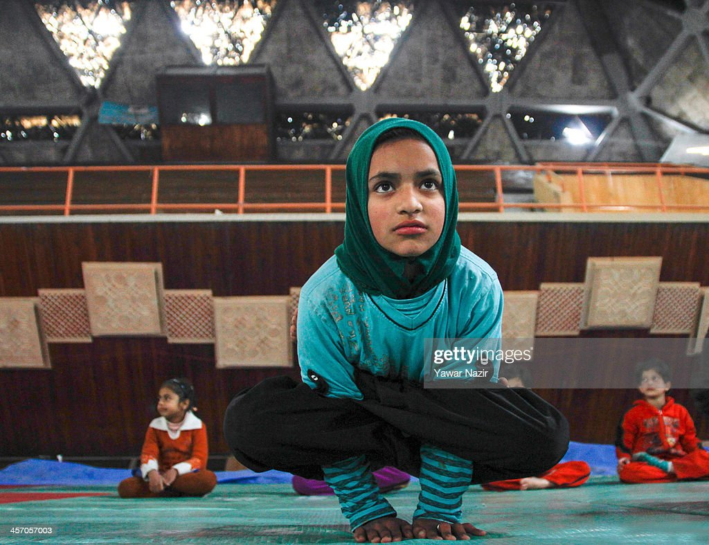 A Kashmiri Muslim young girl learn to balance herself on her hands inside indoor stadium on December 16, 2013 in Srinagar, the summer capital of Indian administered Kashmir, India. As the number of crimes against women has risen in the region, girls from different age groups and backgrounds have taken up martial arts and other self defence courses to thwart attackers. Many believe after the barbaric rape and murder of a para-medic student last year on this day in the Indian capital of New Delhi, women in the Muslim majority state have taken to various martial arts forms like Thang-ta, a weapon-based Indian Martial art for protection.