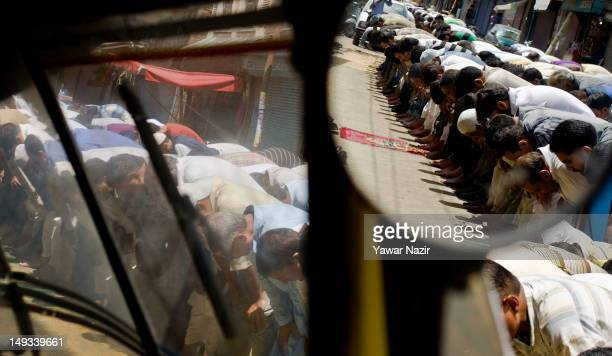 Kashmiri Muslims are reflected in a mirror of an auto rickshaw while offer prayers on a roadside during the first Friday of Ramadan on July 27 2012...