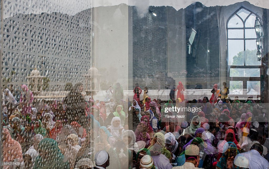 Kashmiri Muslims are reflected on the glass of shrine as they at the the Hazratbal Shrine on the Friday following MehrajuAlam which marks ascension...