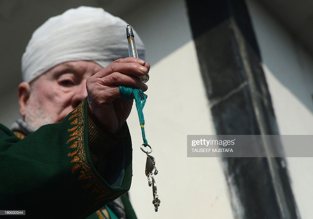 Kashmiri Muslims cleric Peer Hisam-u-Din-Banday displays a holy relic believed to contain a hair from the beard of Prophet Mohammed during Eid-e-Milad-un-Nabi, the birthday of the prophet, at the Hazratbal Shrine in Srinagar on January 25, 2013. Thousands of Kashmiri Muslims gathered at the shrine in the summer capital of Jammu and Kashmir to offer prayers on the Prophet's birth anniversary. AFP PHOTO/Tauseef MUSTAFA