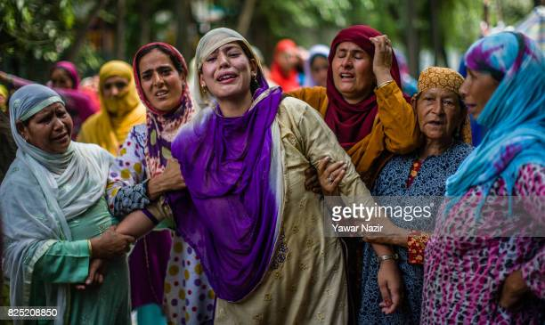 Kashmiri Muslims console the pregnant wife of Firdous Ahmad a civilian killed near the site of a gun battle during his funeral on August 01 2017 in...