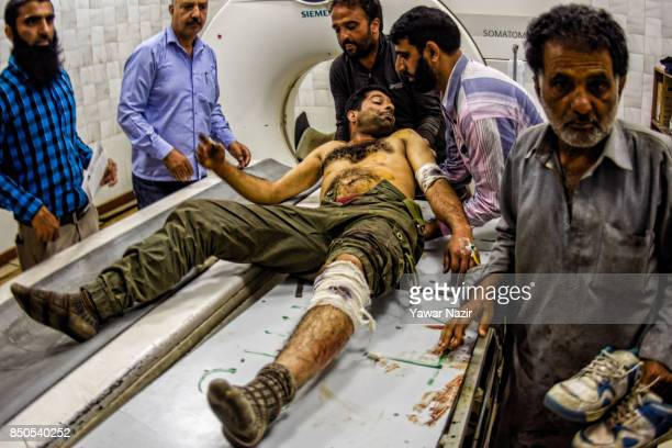 Kashmiri Muslims help a wounded civilian inside a hospital after a grenade attack in a busy market which killed three civilians on September 21 in...