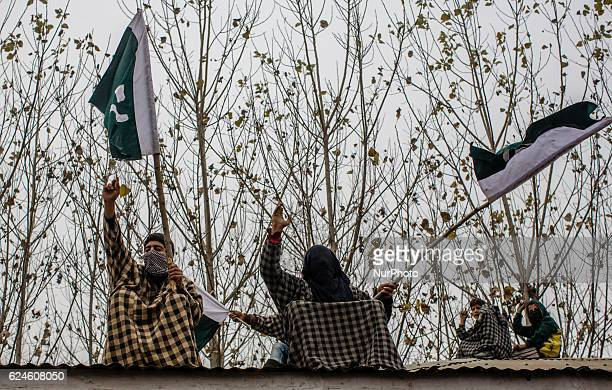 Kashmiri Muslims hold flags on roof tops as they shout anti Indian and Pro Kashmir freedom slogans while attending the funeral of Rayees Ahmad a...