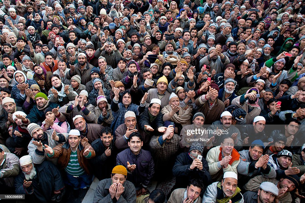 Kashmiri Muslims look towards a cleric (not seen in the picture) displaying the holy relic believed to be the hair from the beard of the Prophet Mohammed at Hazratbal shrine during Eid-e-Milad, the anniversary of the birth of the Prophet Mohammed January 25, 2013 in Srinagar, the summer capital of Indian administered Kashmir, India. Thousands of Muslims from different parts of Kashmir will visit the Hazratbal shrine in Srinagar to pay obeisance on the occasion of Eid-e-Milad. The shrine is highly revered by Kashmiri Muslims as it is believed to house a holy relic of the Prophet Mohammed. The relic is displayed to the devotees on important Islamic days such as the Eid- Milad when Muslims worldwide celebrate the Prophet Mohammed.