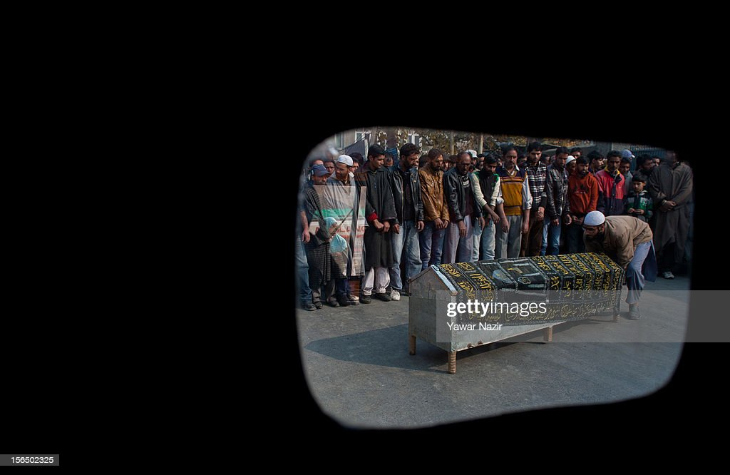 Kashmiri Muslims offer funeral prayers next to the coffin containing the body of Mushtaq Ahmad Dar, who was killed in a suspected militant attack on November 16, 2012 in Srinagar, the summer capital of Indian administered Kashmir, India. Dar, a 33-year- old salesman, was killed and four others wounded when unidentified gunmen opened fire on a liquor shop in Dalgate area of the city on Thursday evening. Liquor shops have faced attacks from militant groups in the past.