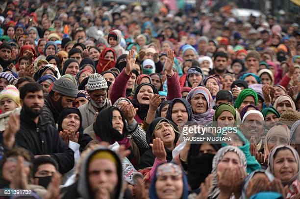 Kashmiri Muslims offer prayers as a priest displays a relic at the shrine of Sheikh Abdul Qadir Geelani in Srinagar on January 10 2017 Devotees are...
