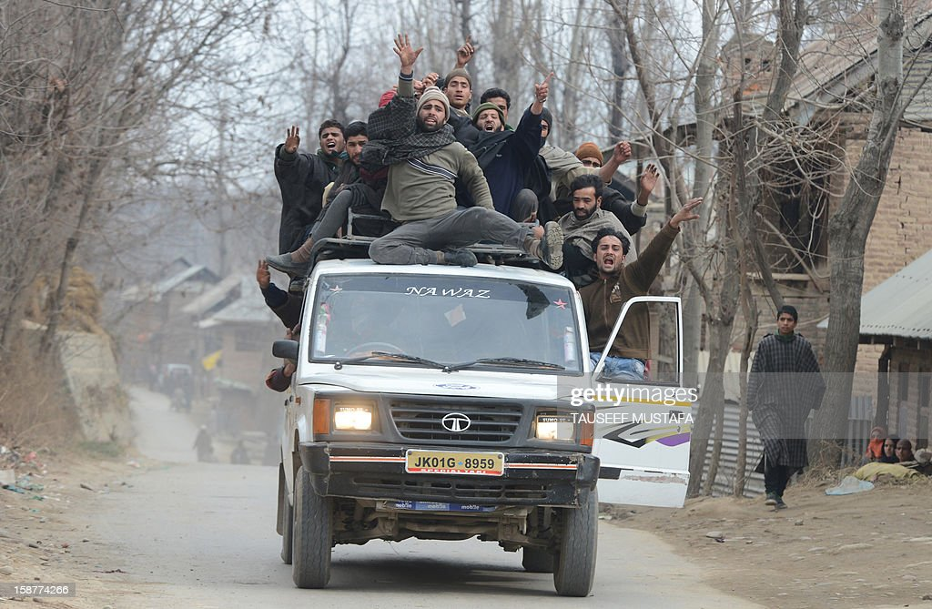 Kashmiri Muslims on the top of a vehicle shout pro-freedom slogans while carrying an injured civilian inside a vehicle in Pulwama some 55kms south of Srinagar on December 28,2012. Indian troops shot dead two suspected Islamic militants in Kashmir while seven civilians received police bullet injuries when they protested the slaying of the rebels, officials said. The two militants belonging to the Pakistan-based Lashkar-e-Taiba rebel group were killed while three troopers were wounded in a firefight with militants in Pulwama town.AFP PHOTO/ Tauseef MUSTAFA