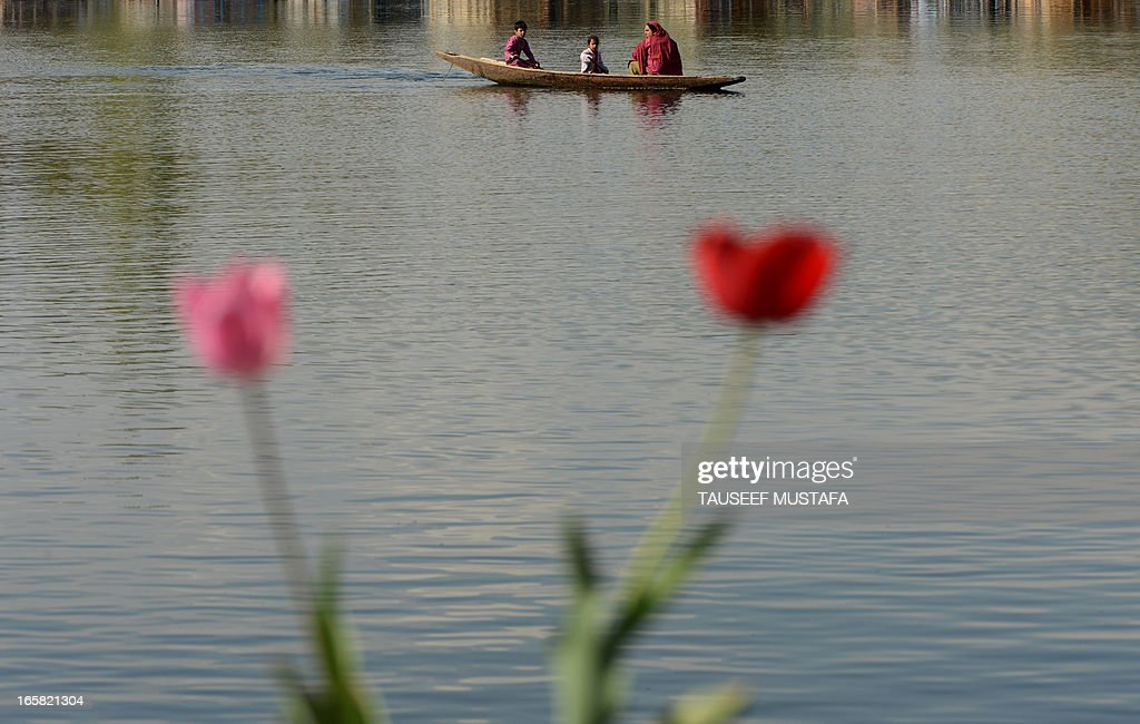 Kashmiri Muslims paddle near the house boat where a young British woman was found murdered is seen in Srinagar on April 6, 2013. A British woman holidaying in Indian Kashmir was found dead 'in a pool of blood' on a houseboat and a Dutch man has been arrested on suspicion of her murder, police said on Saturday. The 43-year-old Dutch national was taken into custody as he tried to flee the scenic Kashmir valley in the foothills of the Himalayas, police superintendent Tahir Sajjad told AFP. AFP PHOTO/Tauseef MUSTAFA