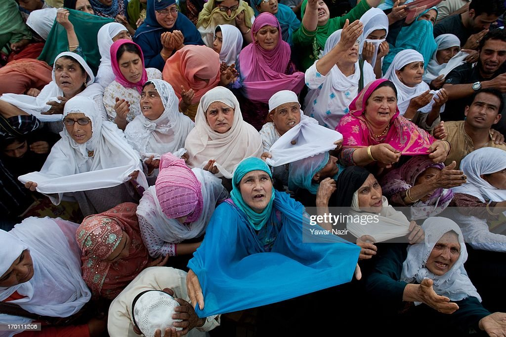 Kashmiri Muslims pray as a head priest (not seen in the picture) displays the holy relic believed to be the hair from the beard of the Prophet Mohammed on the occasion of the Muslim festival Mehraj-u-Alam, which marks ascension day, the journey from Heaven to Earth of the Prophet Mohammed, at the Hazratbal Shrine on June 07, 2013 in Srinagar, the summer capital of Indian administered Kashmir, India. Every year thousands of Muslim devotees from across Kashmir throng the Hazratbal shrine in central Srinagar for prayers and to have a glimpse of the Moi-e-Muqaddas, Holy Relic of Prophet Mohammed, displayed for public viewing on ten occasions in a year , including Meraj-ul Alam , the night Muslims believe Prophet Mohammed ascended to the heaven.