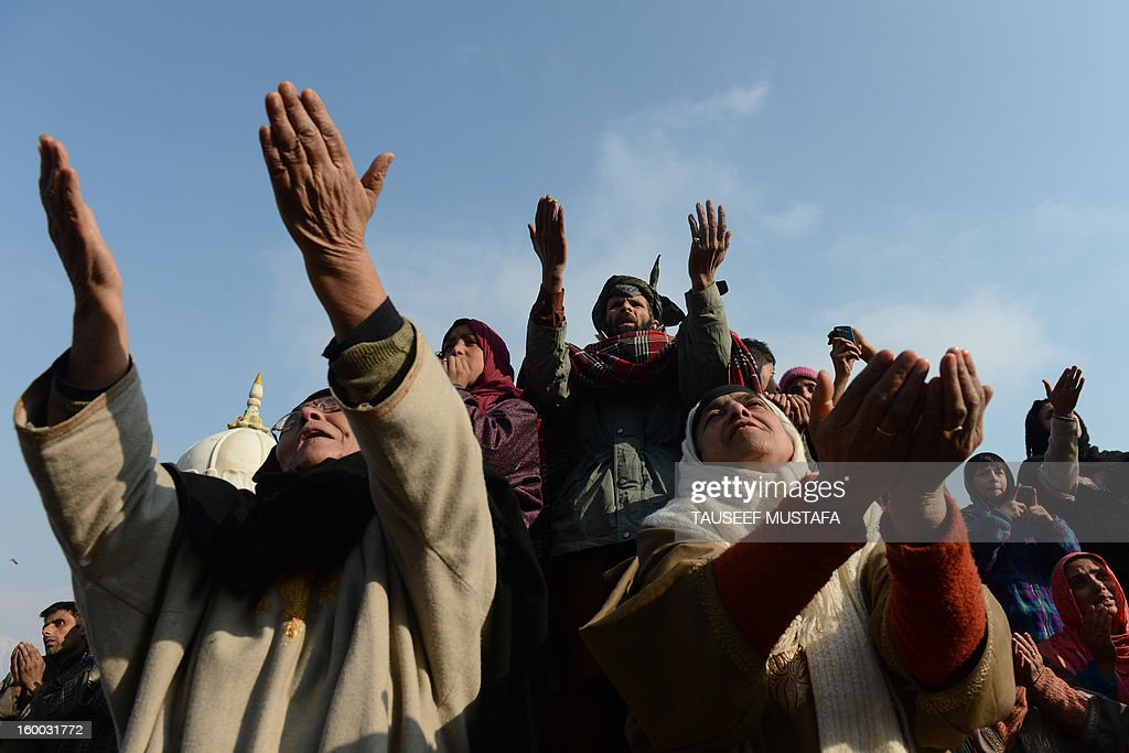 Kashmiri Muslims react as an unseen priest shows a relic believed to be a hair from the beard of Prophet Mohammed during Eid-e-Milad-un-Nabi, the birthday of the prophet, at the Hazratbal Shrine in Srinagar on January 25, 2013. Thousands of Kashmiri Muslims gathered at the shrine in the summer capital of Jammu and Kashmir to offer prayers on the Prophet's birth anniversary. AFP PHOTO/Tauseef MUSTAFA