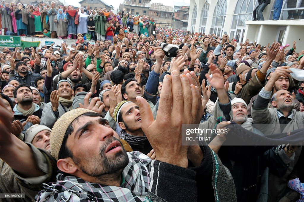 Kashmiri Muslims react as an unseen priest shows a relic believed to be a hair from the beard of Prophet Mohammed at the Hazratbal Shrine in Srinagar on Febuary 1,2013. Thousands of Kashmiri Muslims gathered at the shrine in the summer capital of Jammu and Kashmir to offer prayers and receive blessings. AFP PHOTO/Rouf BHAT