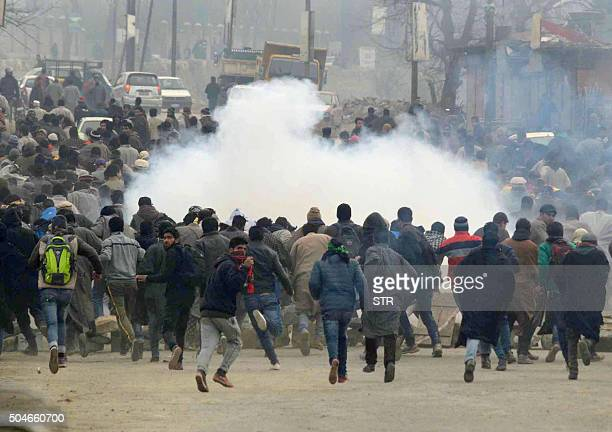TOPSHOT Kashmiri Muslims run as Indian police fire tear smoke shells during the funeral procession of suspected rebel commander Sajad Ahmed Bhat on...