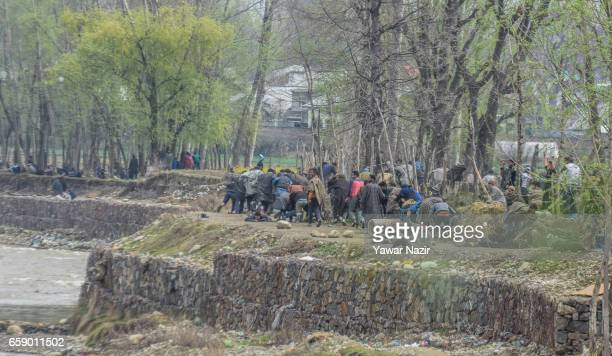 Kashmiri Muslims run for cover as Indian government forces fire at them as they tried to march towards gun battle site during a gun battle between...